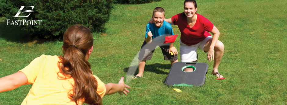 a family playing cornhole on green grass outside
