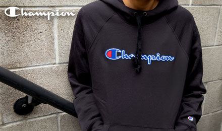 Shop Champion Apparel - person wearing a black Champion sweatshirt leaning against a block wall