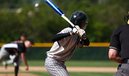 a youth baseball player about to swing at a pitch during a baseball game
